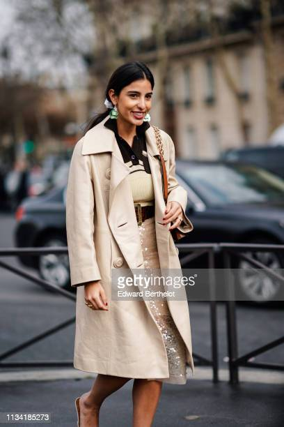 Bettina Looney wears earrings a beige leather coat a black and beige top a glittering sequined beige skirt outside Miu Miu during Paris Fashion Week...
