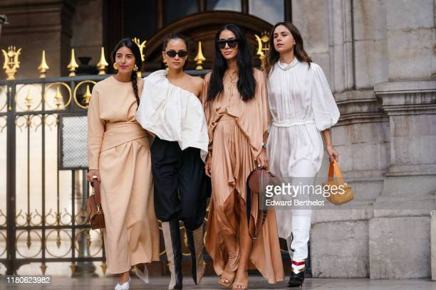 Bettina Looney wears earrings, a beige long dress, a brown bag, white pointy pumps ; Anna Rosa VItiello wears sunglasses, a gathered flowing...