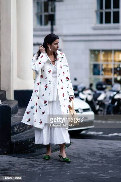Bettina Looney wears earrings a white floral print coat a rectangular bag green shoes during London Fashion Week February 2019 on February 18 2019 in...