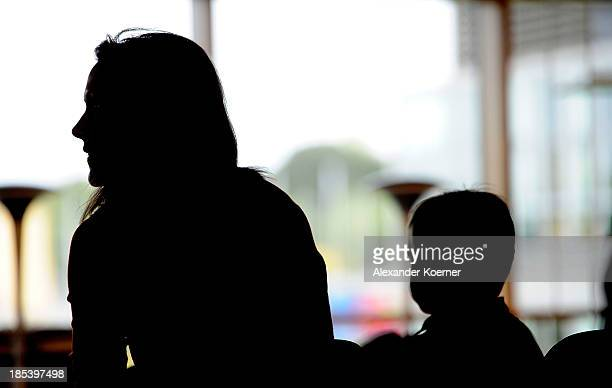 Bettina Wulff sits togehter with her son Linus prior a church service at the Expowal on October 20, 2013 in Hanover, Germany. The church service is...