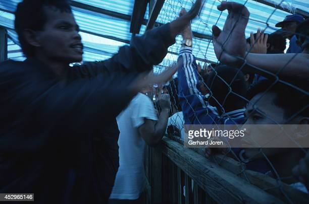 Betting is taking place at a cock fight in Diwalwal. The Diwalwal gold mining community is built on stilts along the hill slopes, without any water...
