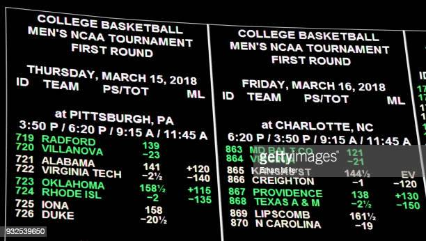 Betting lines for college basketball games are displayed during a viewing party for the NCAA Men's College Basketball Tournament inside the...