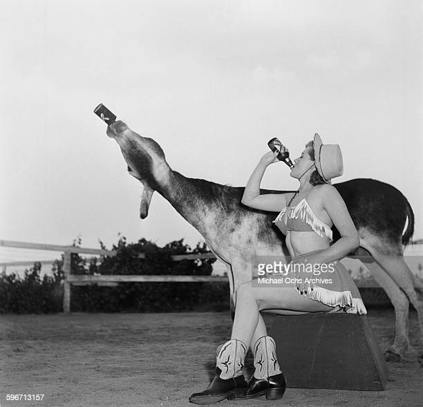 Betty Ames and her donkey Jackson drink from a bottle in Los AngelesCalifornia