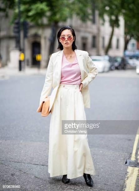 Betty Bachz wearing creme wide leg pants, blazer jacket, clutch is seen during London Fashion Week Men's June 2018 on June 9, 2018 in London, England.