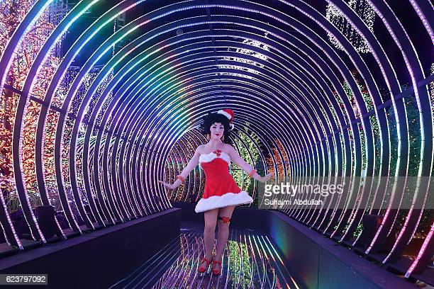 Betty Boop impersonator poses for a photo inside the Rainbow Connection light display during the media preview of Universal Journey a Santa's AllStar...