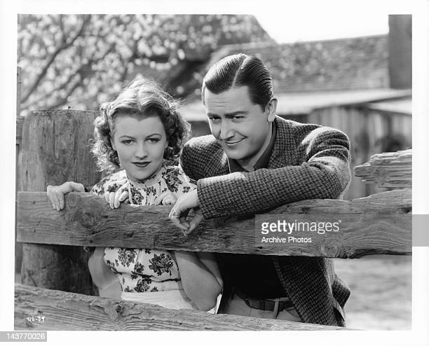 Betty Furness and Robert Young looking over fence post in a scene from the film 'The Three Wise Guys', 1936.