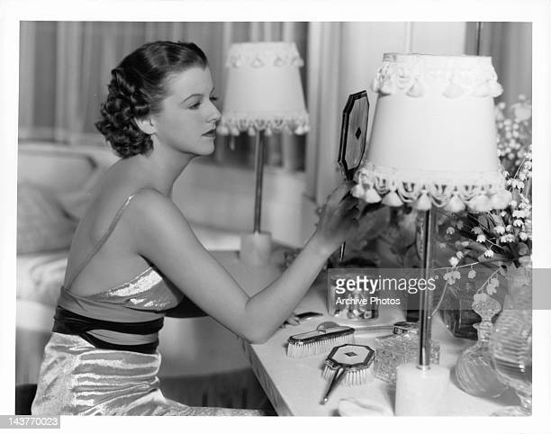 Betty Furness looking at herself in the mirror in a scene from the film 'The Three Wise Guys', 1936.
