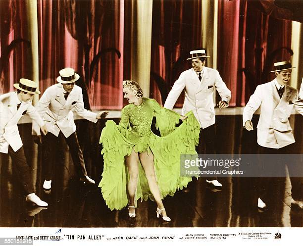 Betty Grable, in a bright green dress, dances with four gents in a still photograph from Tin Pan Alley, Hollywood, California, circa 1929.