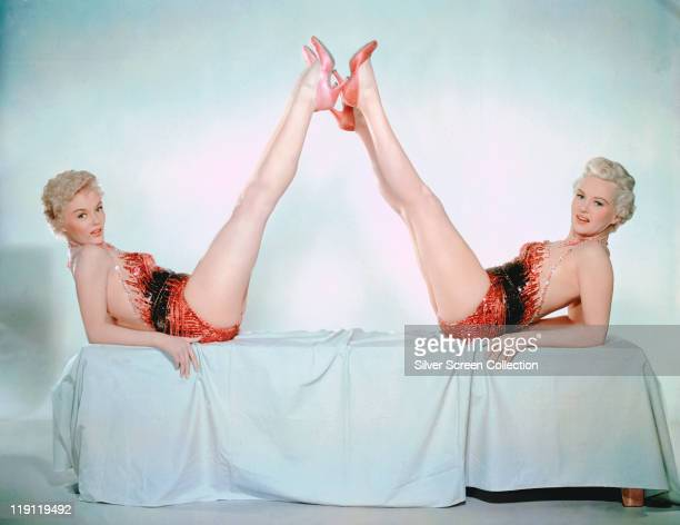 Betty Grable US actress dancer and singer poses wearing a redandblack bodice as she leans back with her legs legs in the air at an angle in a studio...