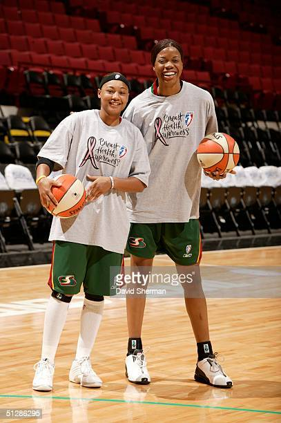 Betty Lennox and Janell Burse of the Seattle Storm wear special tshirts celebrating WNBA Breast Health Awareness Day during pregame warmups prior to...