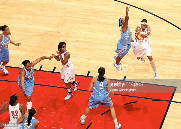 Betty Lennox of the Atlanta Dream passes the ball under pressure against Jia Perkins of the Chicago Sky watch the action from the bench during the...
