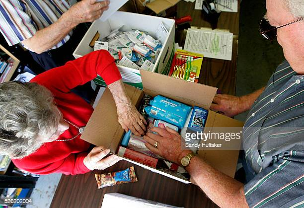 Betty Tenney and Dan May load a care package to be sent to troops overseas in a garage at the La Costa Glen Retirement Community where they live in...