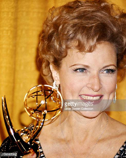 Betty White US actress smiling as she holds an Emmy Award against a yellow background USA circa 1975