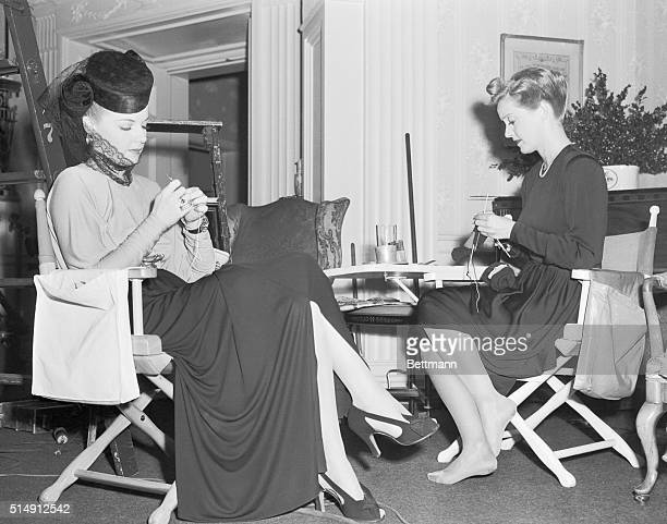 Between appearances Ann Sheridan left and Bette Davis industriously ply knitting needles For complete relaxation Bette has slipped her shoes off Ann...