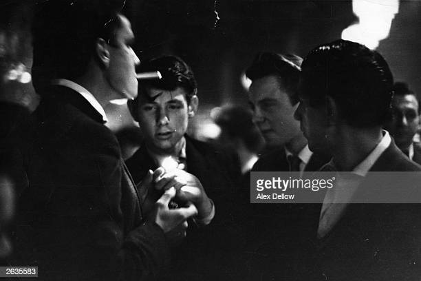 Between dances the 'Teddy Boys' group themselves into all male parties and enjoy a cigarette Original Publication Picture Post 7169 The Truth About...