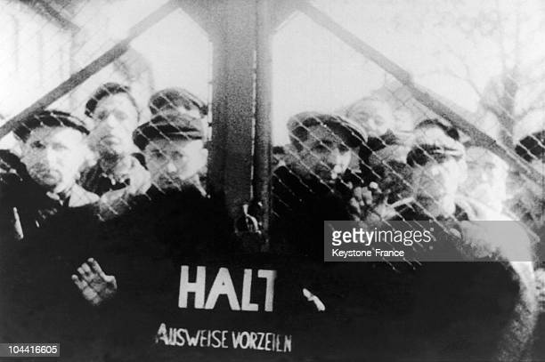 Between January 26 and 27 some survivors dispersed behind the gates of the camp at AUSCHWITZ are watching the arrival of Soviet troops who have come...