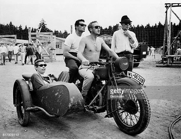 Between takes on the film The Great Escape Steve McQueen in the driver's position on a motorcycle with James Garner behind him and James Coburn in...