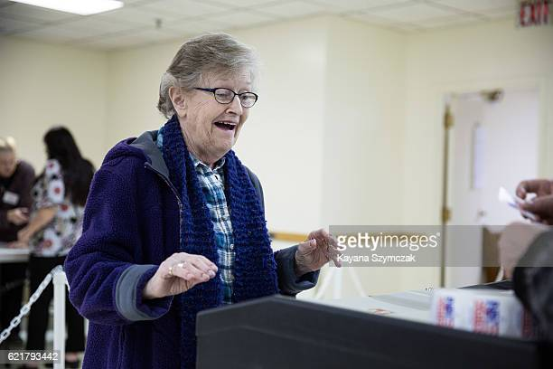 Bev Heath casts her ballot into the ballot box at the Immaculate Conception Church on November 8 in Penacook New Hampshire Americans today will...