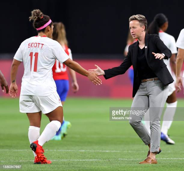 Bev Priestman, Head Coach of Team Canada celebrates with Desiree Scott of Team Canada after victory in the Women's First Round Group E match between...