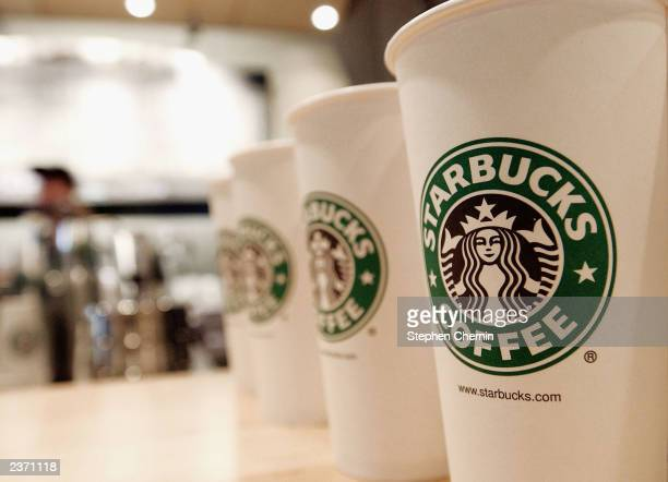 Beverage cups featuring the logo of Starbucks Coffee are seen in the new flagship store on 42nd Street August 5 2003 in New York City The...