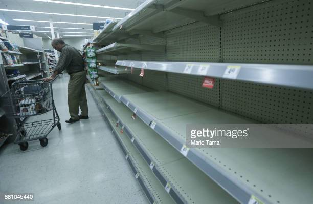 Beverage shelves stand mostly empty in a Walgreen's store over three weeks after Hurricane Maria hit the island on October 13 2017 in San Juan Puerto...
