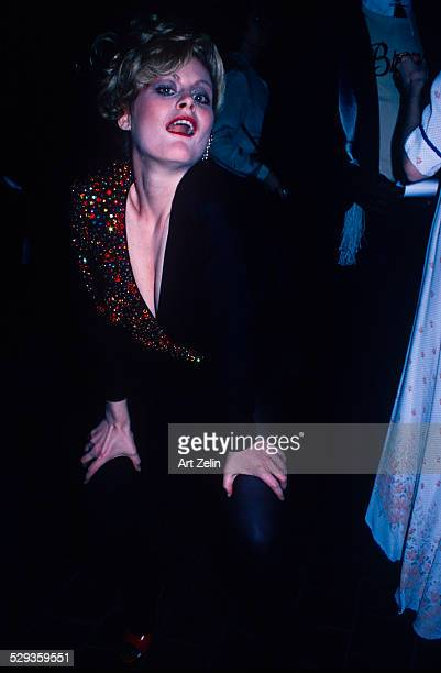 Beverly D'Angelo posing for the photographer wearing a black dress with beaded collar circa 1970 New York