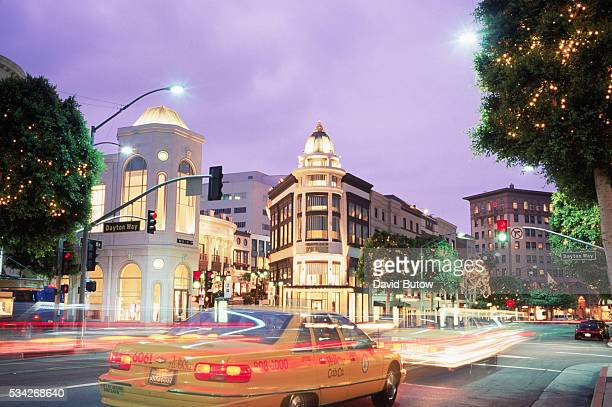 Beverly Hills' bustling Rodeo Drive Shopping Center as seen at dusk.