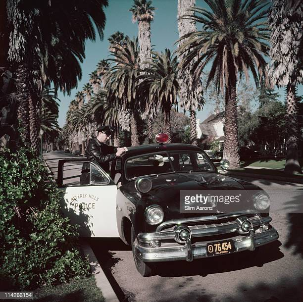 Beverly Hills police patrolman Lee R Hathaway leaning on the roof of his car to write a report Bedford Drive Beverly Hills California 1952