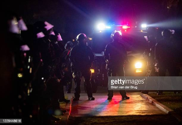 Beverly Hills police stand ready as a group of Trump supporters wave flags and cheer at a gathering in Beverly Gardens Park on Santa Monica Blvd. At...