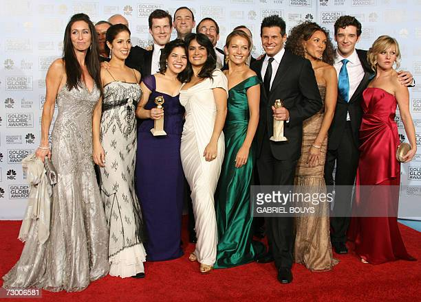 US actress America Ferrera presenter Selma Hayek and the cast and crew of the US television show 'Ugly Betty' pose backstage at the Golden Globe...