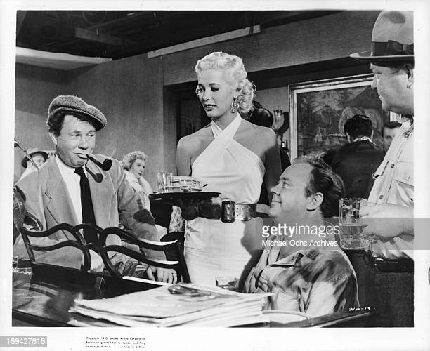 Beverly Michaels bringing men drinks in a scene from the film 'Wicked Woman' 1953