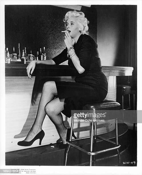 Beverly Michaels smoking cigarette at bar in a scene from the film 'Wicked Woman' 1953