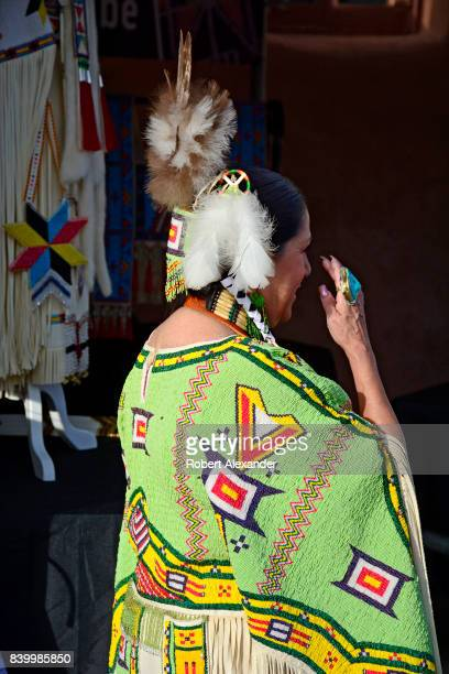 Beverly Moran, a Native American artist from Standing Rock Sioux Reservation, stands with her traditional beaded clothing in her booth at the Santa...