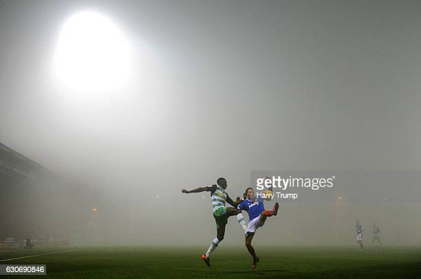 Bevis Mugabi of Yeovil Town and Kal Naismith of Portsmouth vie for the ball as the fog settles during the Sky Bet League Two match between Yeovil...