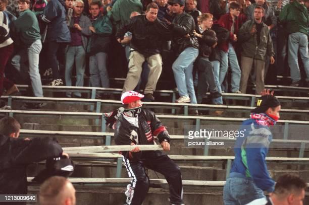 Bewaffnet mit einer aus den Sitzreihen herausgerissenen Latte treibt ein deutscher Hooligan während des Fußball-Länderspielspiels Polen - Deutschland...