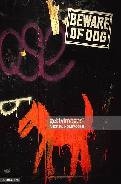 A 'Beware of Dog' sign is found on a wall next to a painting of a dog