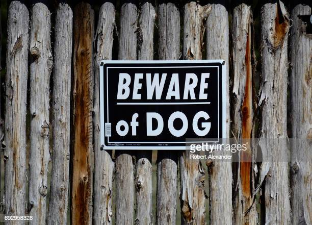 A 'Beware of Dog' sign is mounted to a rustic yard fence in Santa Fe New Mexico