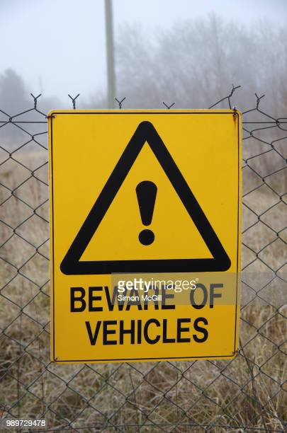 'beware of vehicles' sign on a chainlink fence around a vacant lot - chainlink fence stock pictures, royalty-free photos & images