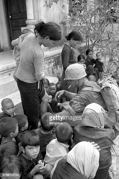 Bewilderment is mirrored in the faces of the children as a US Marine goes about the business of searching a young Vietnamese mother in a village...