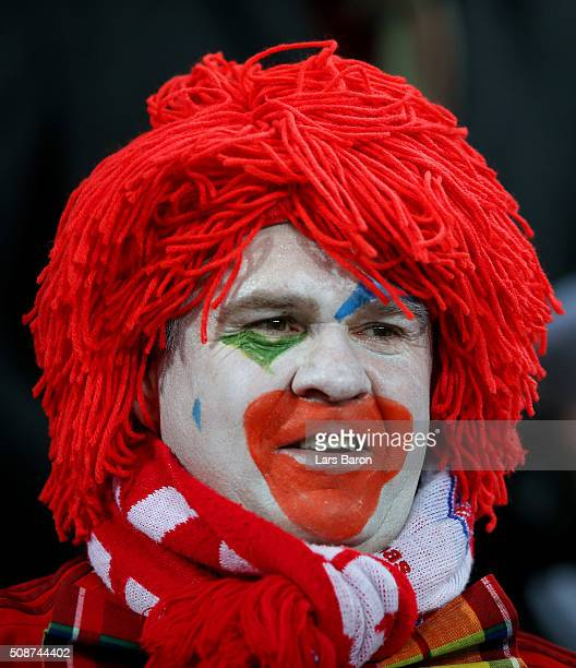 Beyern Muenchen fan dressed as a clown looks on from the stands before the Bundesliga match between Bayer Leverkusen and FC Bayern Muenchen at...