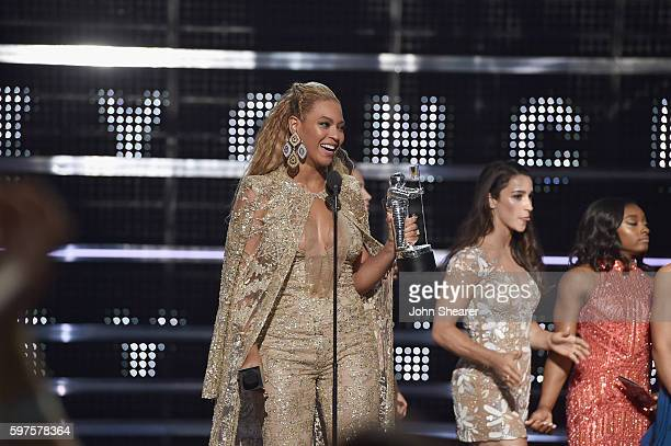 Beyonce accepts an award onstage from Aly Raisman and Simone Biles onstage during the 2016 MTV Music Video Awards at Madison Square Gareden on August...