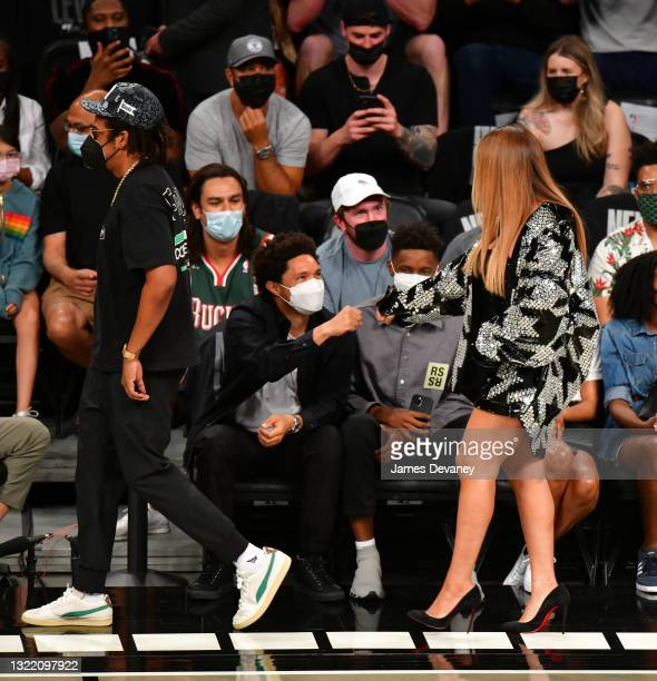 Beyonce fist bumps Trevor Noah as she and Jay-Z attend Brooklyn Nets v Milwaukee Bucks game at Barclays Center of Brooklyn on June 05, 2021 in New...