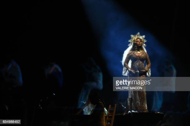 TOPSHOT Beyonce performs as she is pregnant with twins during the 59th Annual Grammy music Awards on February 12 in Los Angeles California / AFP...