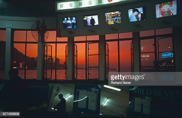 Beyond Chinese TV media images a red sun sinks behind late cloud in the west a glowing red sky illuminates Hong Kong's harbour this scene is symbolic...