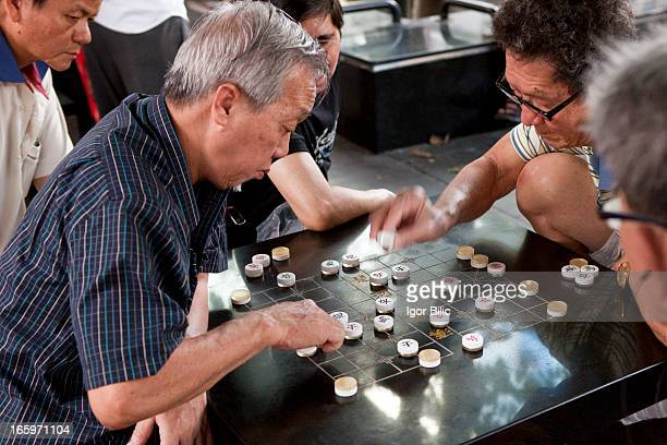 Beyond the business district of Chinatown in Singapore, there is a quiet street where elderly Chinese men play their favorite board game, the xiangqi...