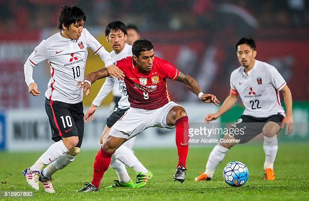 Bezerra Maciel Junior of Guangzhou Evergrande competes for the ball with Kashiwagi Yosuke of Urawa Red Diamonds and Abe Yuki of Urawa Red Diamonds...