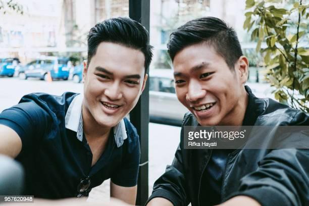 bff - two men taking selfie - rifka hayati stock pictures, royalty-free photos & images