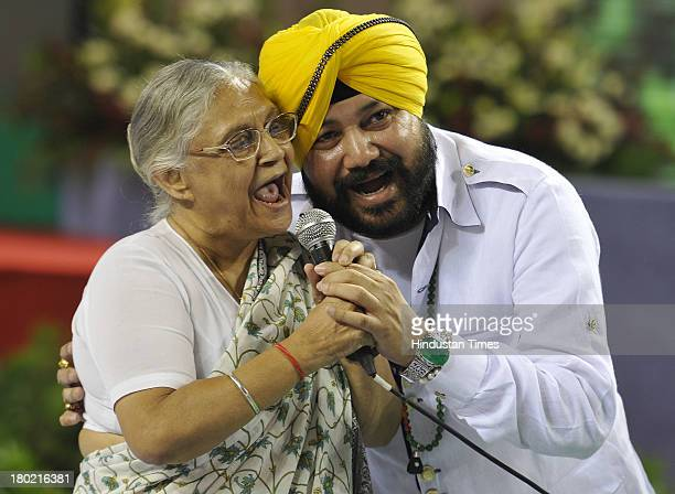 Bhangra pop singer Daler Mehndi singing a song alongwith Delhi Chief Minister Sheila Dikshit during a function to confer ownership rights to the...
