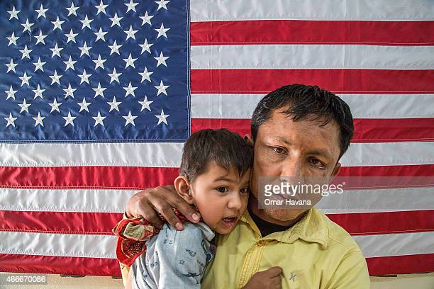 Bhanubhakta Addhikari and his son stand in front of an American National flag inside the cultural orientation class in the Beldangi refugee camp on...