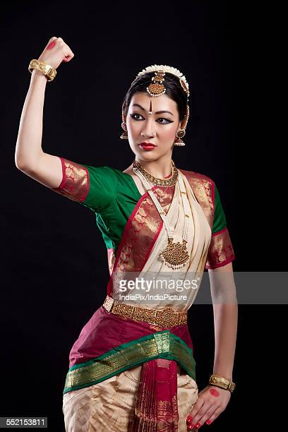 Bharatanatyam dancer flexing muscle over black background